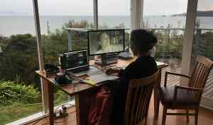 A woman sits with her back to the camera at a desk with a computer editing station in a room with floor to ceiling windows, beyond which lies a green forest and the water horizon of Waratah Bay in Gippsland, Australia.