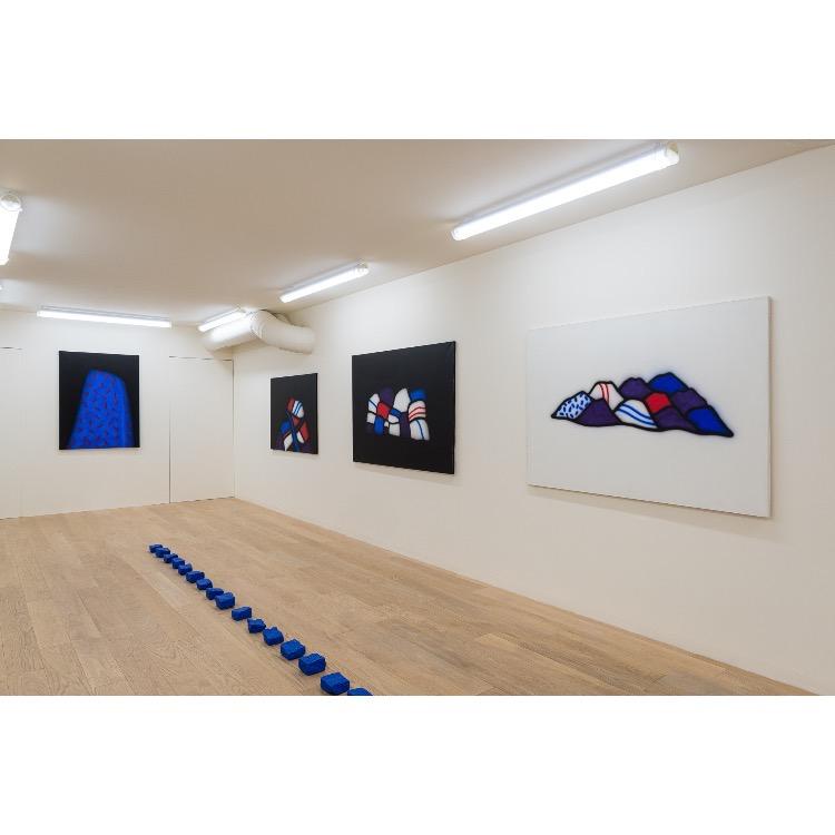 """Vue de l'exposition """"Le Phénomène Verame"""", avec de gauche à droite  : «Sans titre», acrylique sur toile, 1987, «Sans titre», acrylique sur toile, 1987, «Sans titre», acrylique sur toile, 1987, «Sans titre», acrylique sur toile, 1987, «49 pavés de Paris» (d'une série de 50), pavé bleu, 2019. Photographie : © Grégory Copitet - Enseigne des Oudin"""