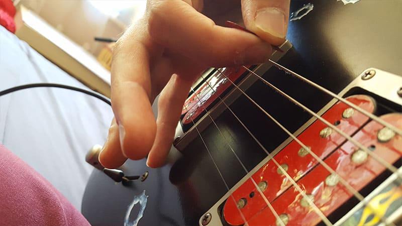 """Photo de la position de la main avec tenue du médiator pour l'article """"Jouer En Palm Mute À La Guitare"""""""