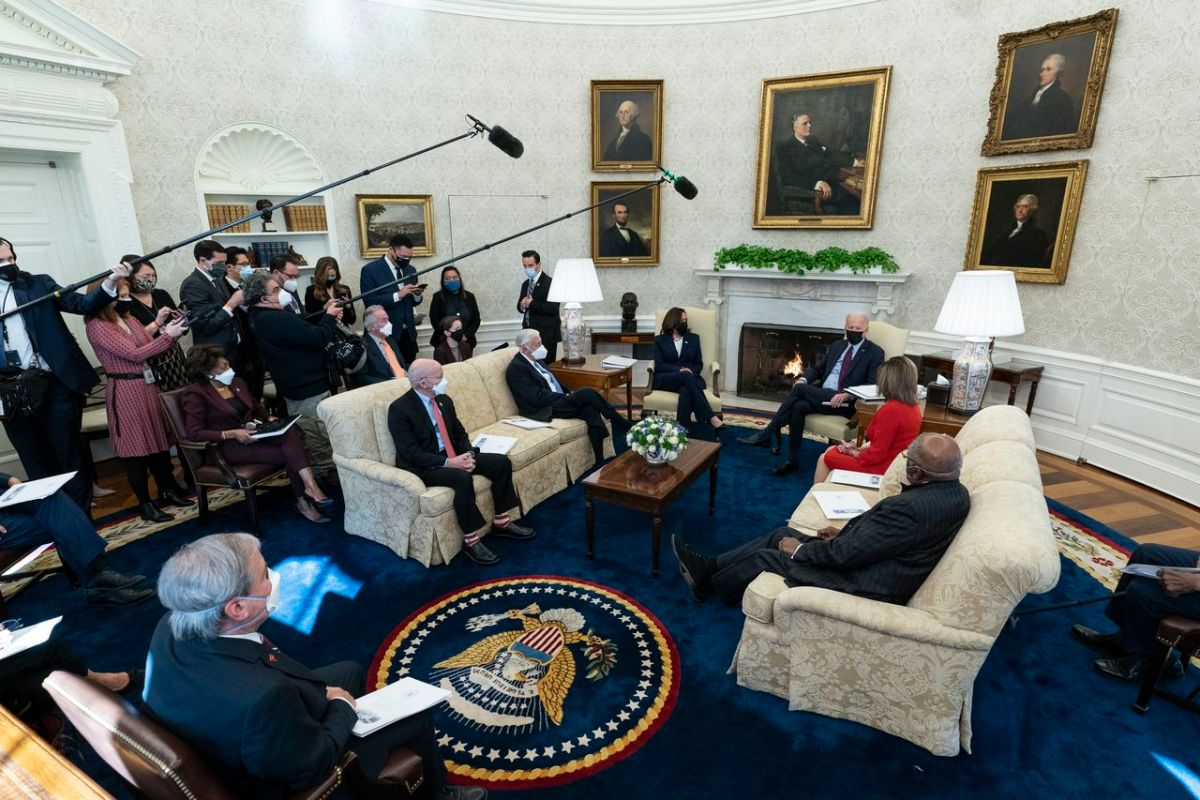 President Joe Biden, accompanied by Vice President Kamala Harris, speaks with House Speaker Nancy Pelosi and House Majority Whip James Clyburn, right, House Majority Leader Steny Hoyer, seated second left, and Rep. Peter DeFazio, D-Ore., seated left, and Rep. John Yarmuth, D-Ky., foreground, in the Oval Office of the White House on Feb. 5, 2021.