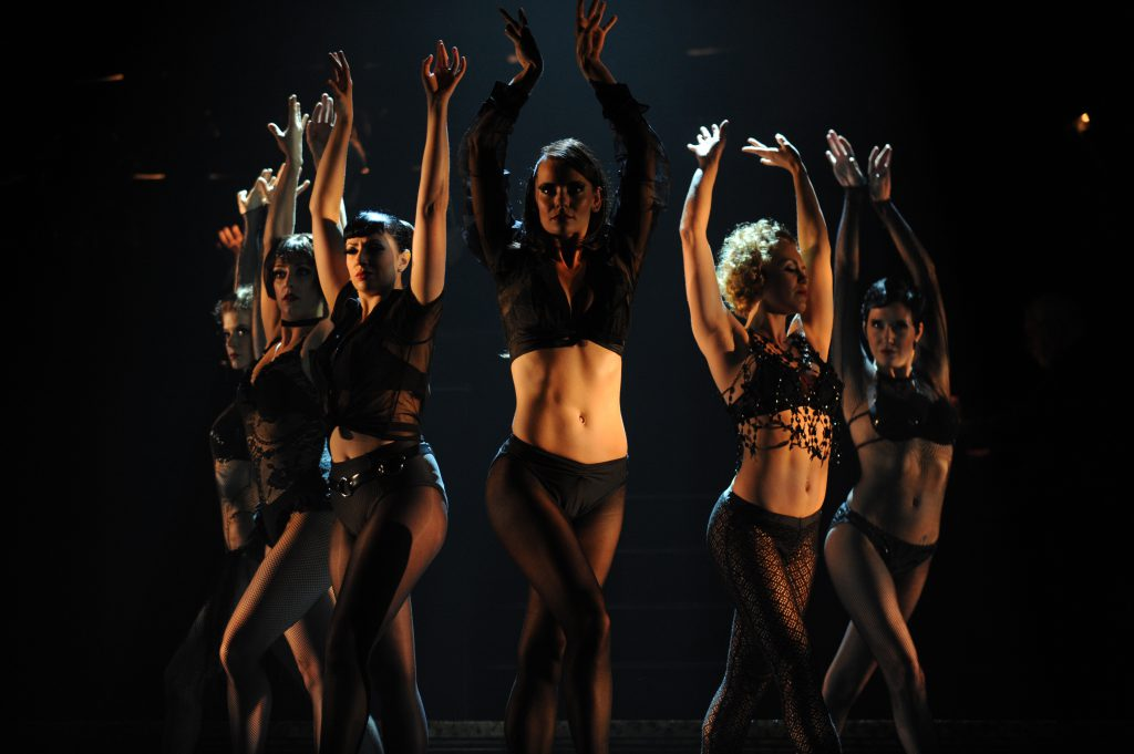Female cast members performing a dance number.