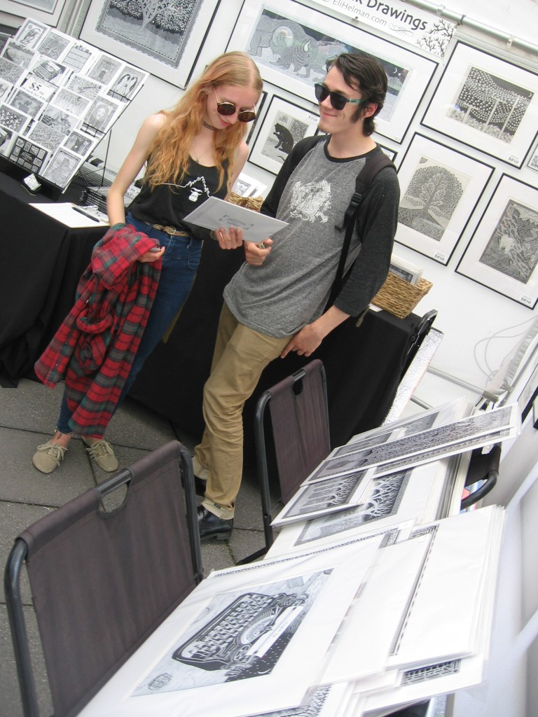 Laura Rosner and Devin Angiolieri, both of Greensburg, are looking at pen and ink drawings by Eli Helman.