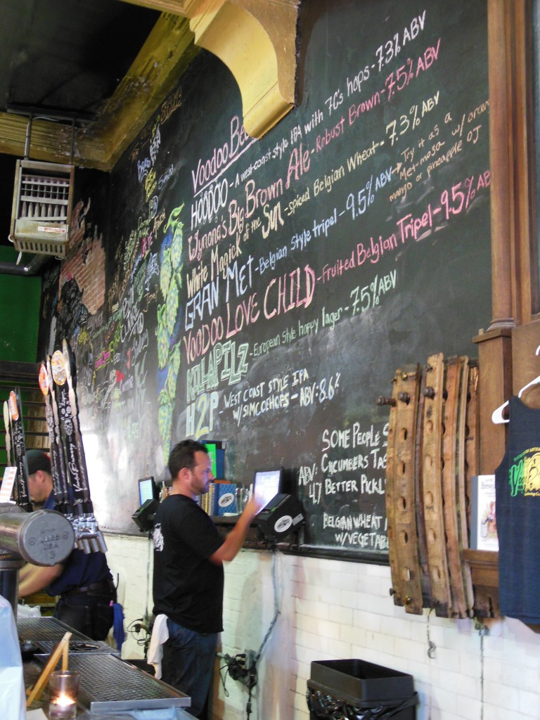 A bartender cashes out a patron beneath the colorful, chalked draft list. Beyond are the names of volunteers who helped get Voodoo Homestead off the ground.