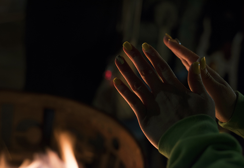 A reveler warms her hands at one of the fires in steel drums along Penn Avenue.