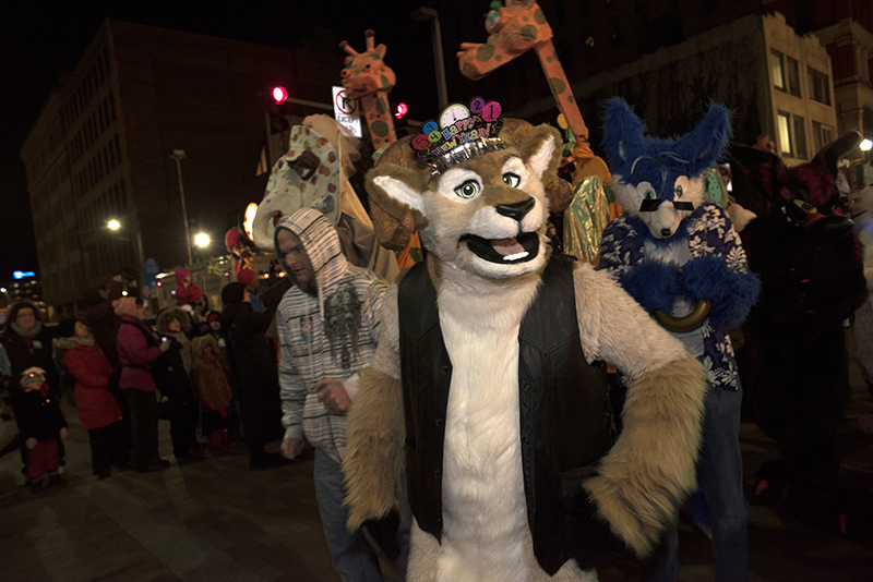 A Furry wishes onlookers a happy new year while marching in the parade.