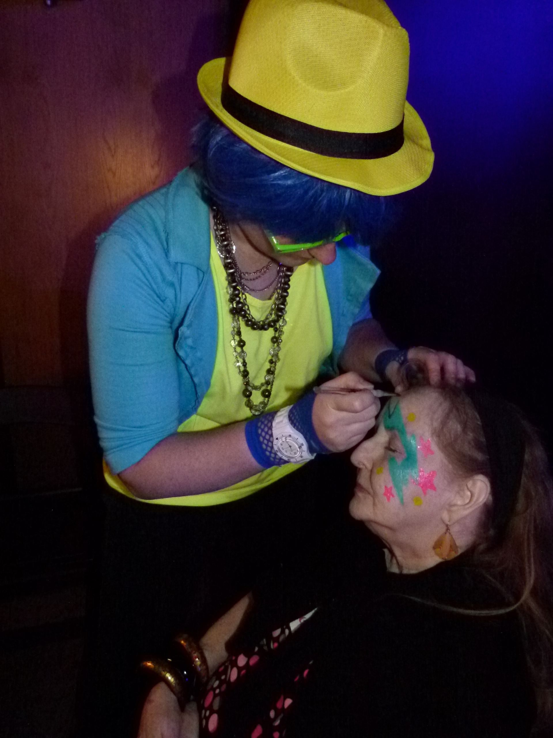 Glam station makeup artist Joyce Swoepe applying party designs to Susan McKee.