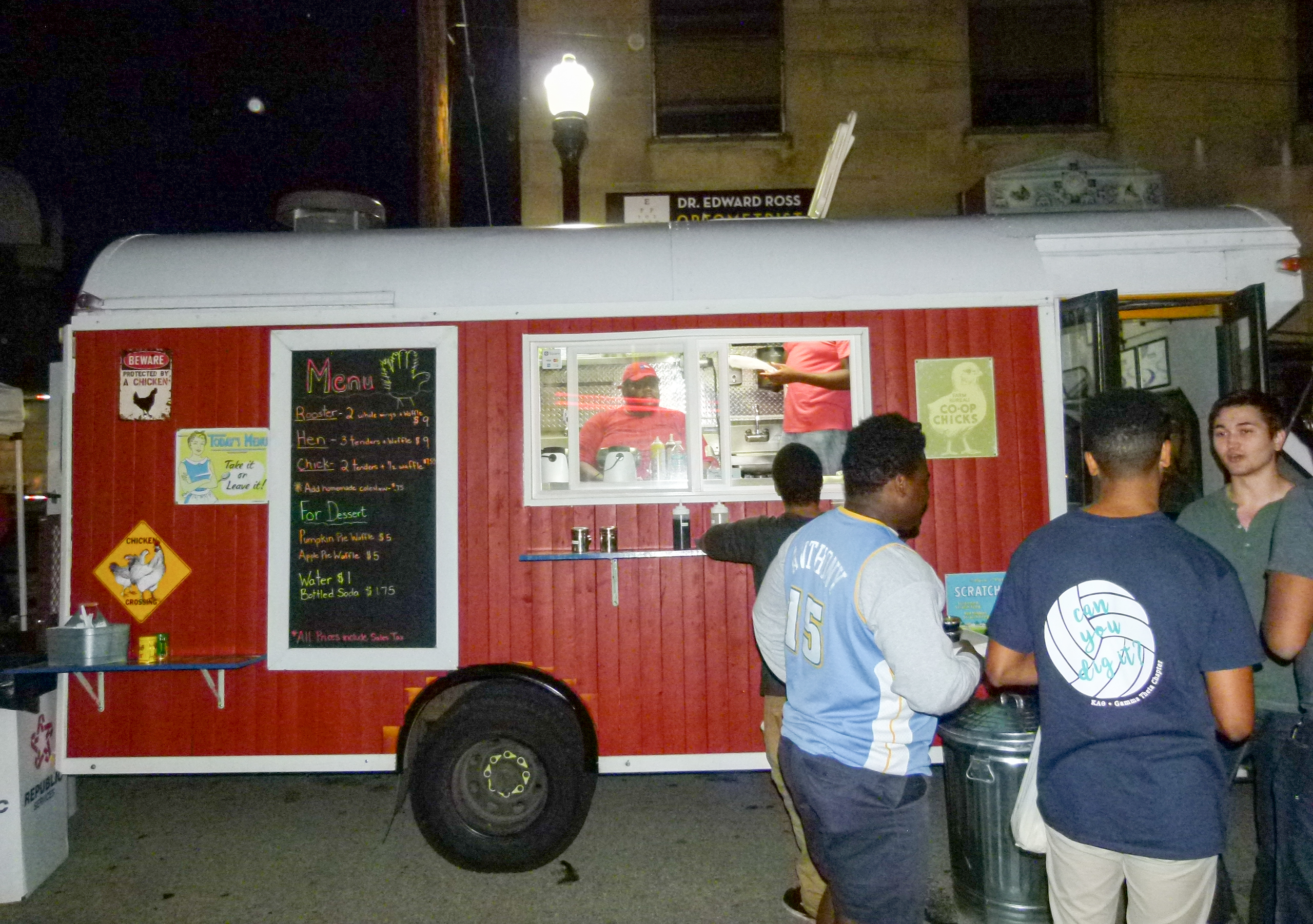 The Coop Chicken and Waffles food truck on the scene. Earsell Fitzgerald (in window) prepares food for a customer while his brother Justin (standing in the truck) restocks. Also working in the truck is Nikki.
