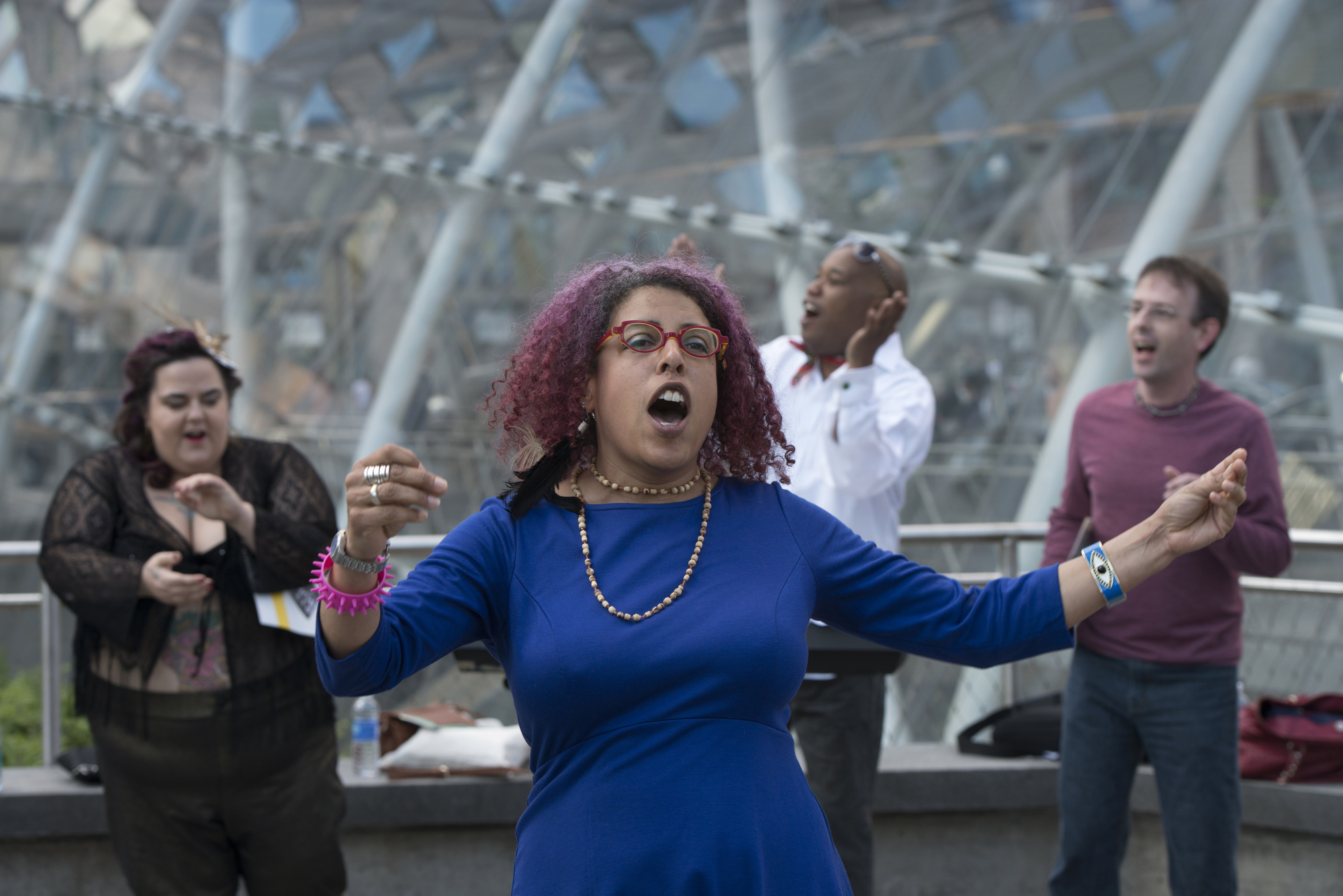 """Performance artist Christiane D leads the Complaints n'at Choir at Gateway Center's """"T"""" Station in downtown Pittsburgh."""