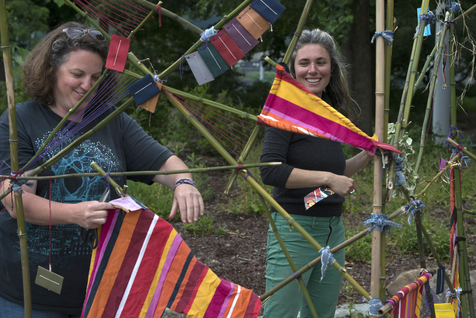 """Assisting artists Jenn Benchak (left) and Jenn Myers (right) add material to Rose Clancy's sculpture """"Diversion"""" at Point State Park."""