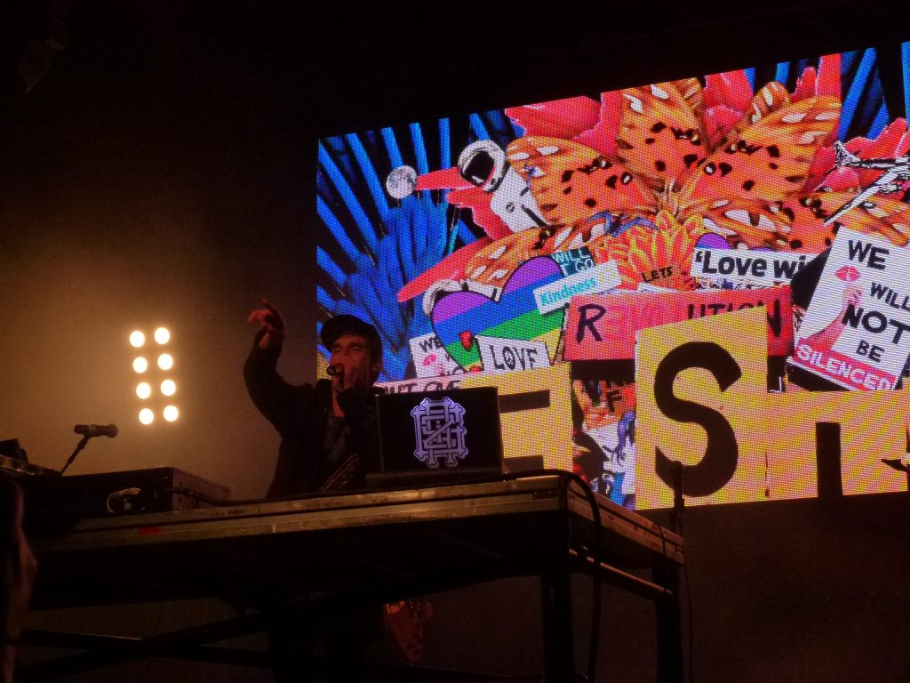 Griz DJing in front of his colorful video imagery.