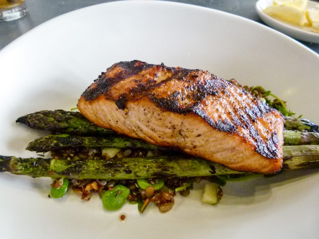 Wood grilled salmon nestled on a bed of asparagus spears.