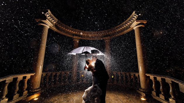 kiss in rain under umbrella