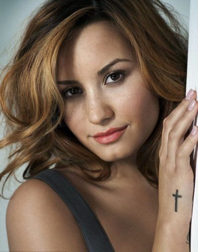 Demi Lovato cross tattoo on side of right hand