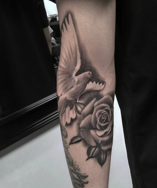 black and white dove with rose tattoo on arm