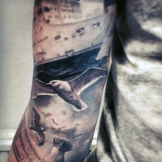 realistic painting with seagulls tattoo on full arm