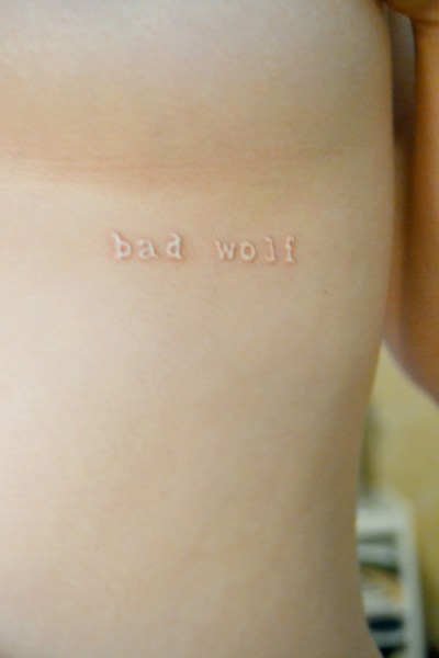 small text white ink tattoo on ribs