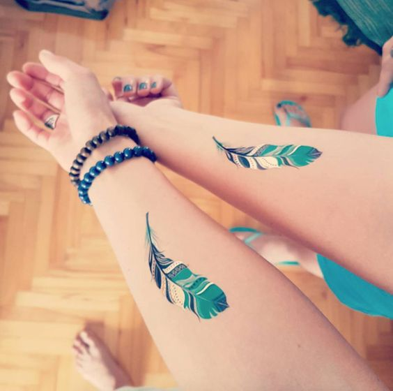 best friends matching feather tattoos on forearm