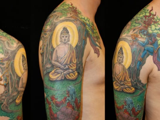 beautiful colorful portrait of bodha under bodhi tree tattoo on men sleeve shoulder