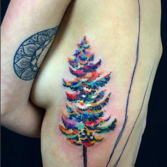 big watercolor evergreen tree tattoo on side ribs for women