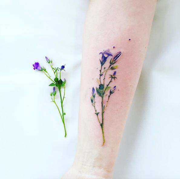 realistic wildflower tattoo on forearm