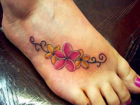 small yellow pink plumeria flowers tribal tattoo design on foot