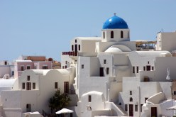 White buildings on the hillside of Santorini island, with a blue dome standing out