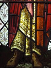 Detail of Stained glass window, St Paul's feet and patterned fabrics