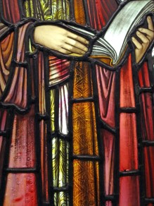 Close up of Stained glass window detail, St Paul's hands holding a book.