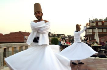 Two dervishes whirling, one with arms outstretched, the other with arms still folded
