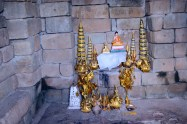 Inside the central tower of Bakong, the inner shrine, showing a small plastic buddha and incense burners