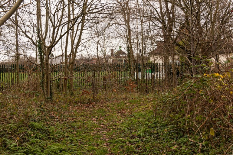 Fencing along the River Quaggy in Sydenham Cottages Nature Reserve, looking towards City of London School Sports Ground