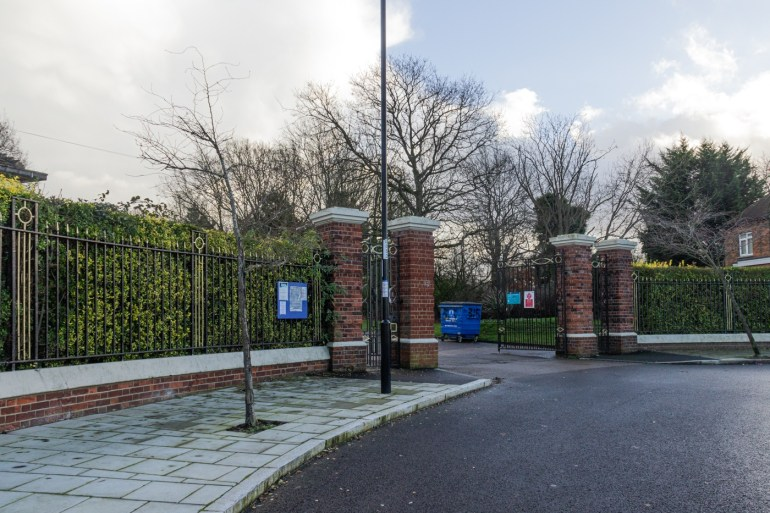Entrance to Grove Park Cemetery through wrought iron gates between brick piers