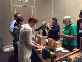 Teachers are shown how to build a home for mason bees using a block of wood and a drill.