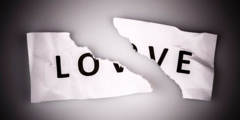 """Love"" word written on torn paper on white"