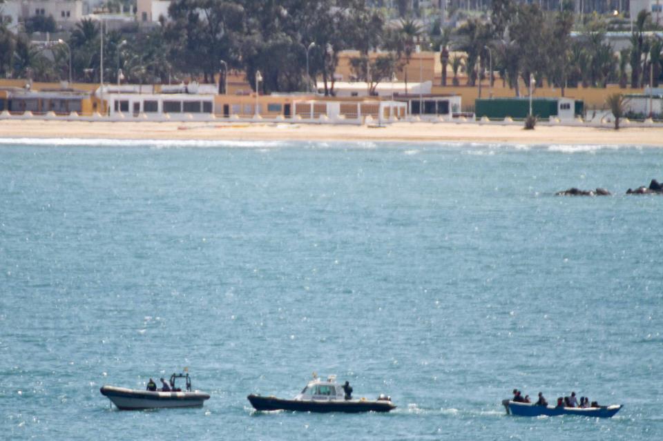 Momento en el que la Guardia Civil traslada la patera al puerto, de fondo el paseo marítimo de Melilla. / J.P