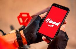Motoboy segurando celular com tela do app iFood aberta
