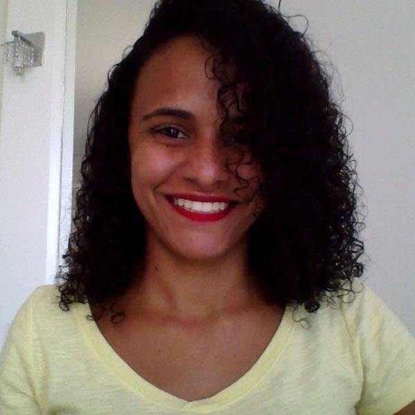 Priscila é negra, tem cabelos cacheados pretos na altura dos ombros. Tem olhos castanhos, usa batom vermelho e sorri. Veste blusa amarela.