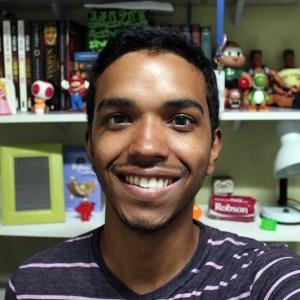 Ele tem a pele morena, cabelos pretos curtos, bigode e barba rala. Ele sorri e veste camisa roxa e lilás. Atrás dele, prateleiras com livros, bonecos e porta retrato.