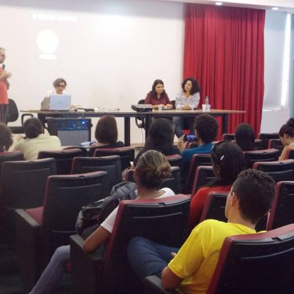 Palestrante Carlos Ferraz à esquerda. De pé, ele segura um microfone. À direita, as professoras Yvana Fechine, Joana Belarmino e Jonara Medeiros. À frente deles, plateia. Cerca de 14 pessoas sentadas em poltronas vermelhas.