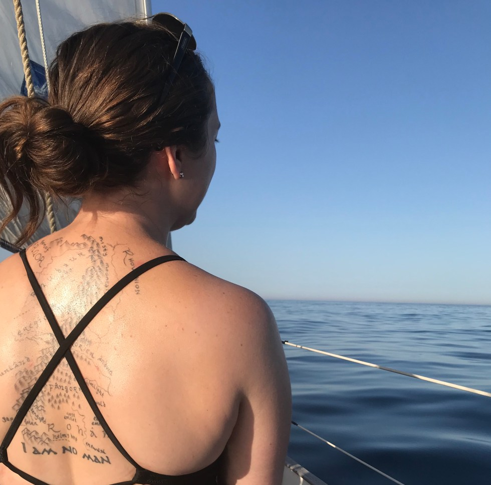 A woman looks out onto the sea from a sailboat