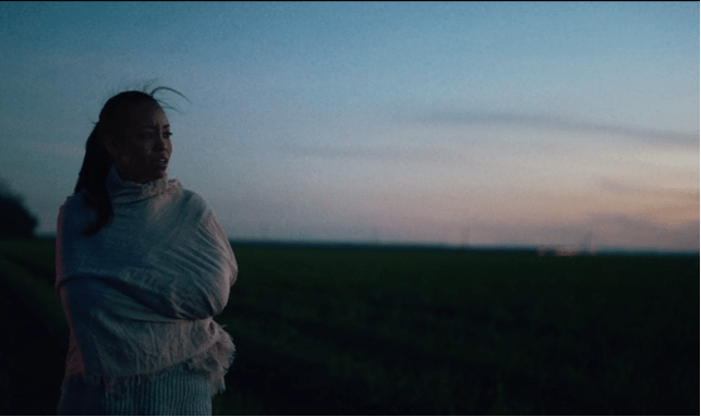 Woman draped in a white shawl looks out to her left on a sugarcane field at sunset.