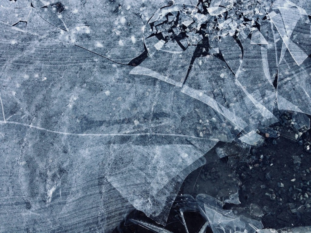 Broken ice of a frozen puddle on shattered asphalt.