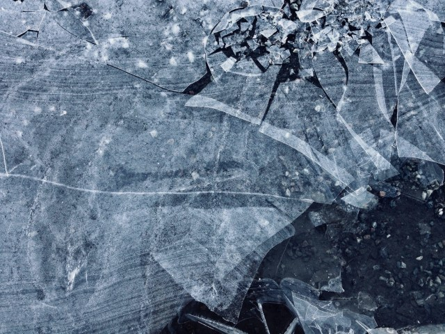 Broken ice of a frozen puddle on shattered asphalt.
