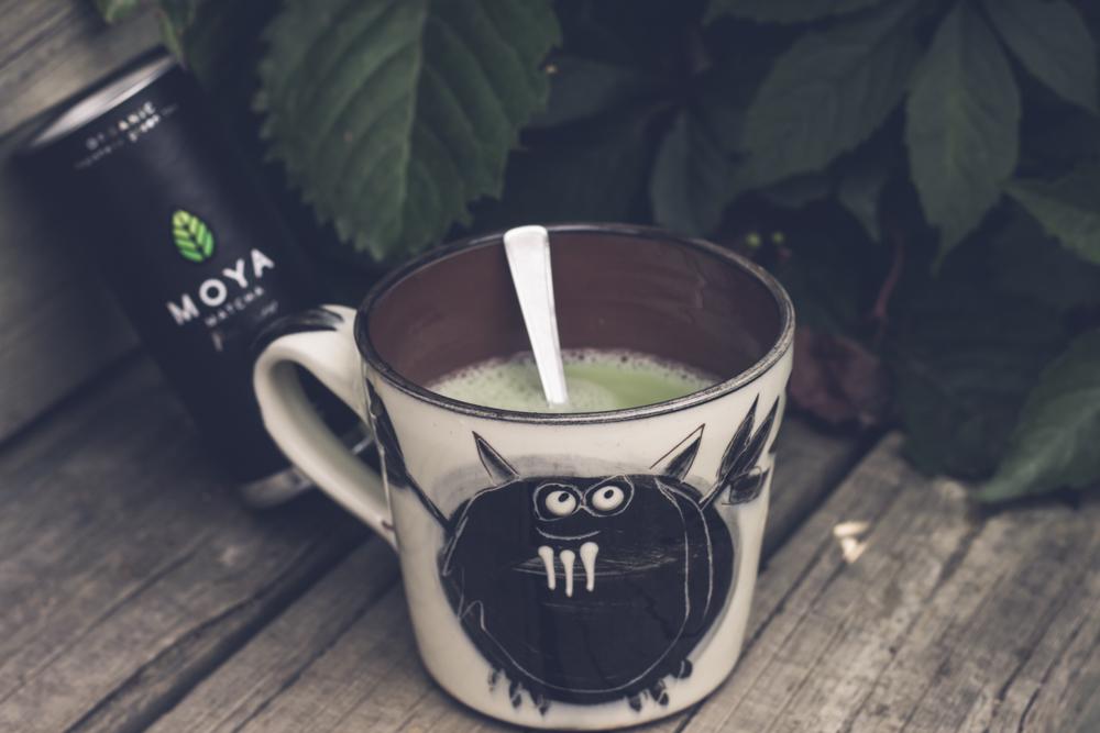 Burk med Moya matcha och mugg med matcha te i, dricka matcha.