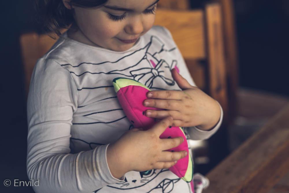 Rensa och skänk med barn. Barn håller i vattenmelon av mjukt material som ska skänkas till välgörenhet.