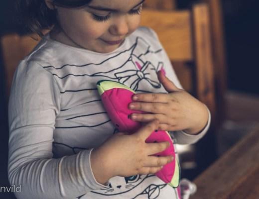 Barn håller i vattenmelon av mjukt material.