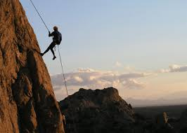Man rappelling down a cliff