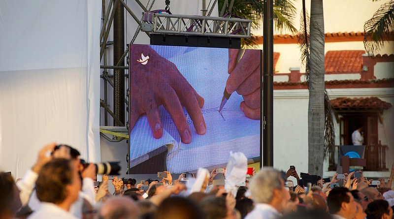 Colombian President Santos Signs a Peace Accord With FARC Leader Jiménez. Pictured: a crowd watches a large screen that shows hands signing a document