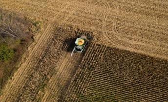 A corn harvester navigates across a field.