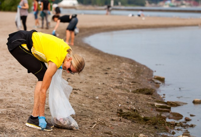Woman picks up litter at beach cleanup